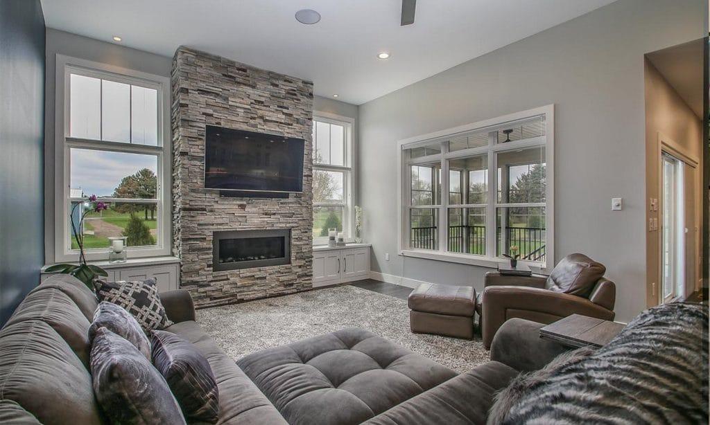 stacked stone fireplace surround large area rug medium hardwood floor