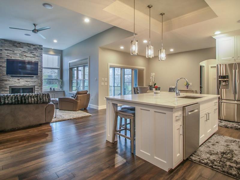 great room hardwood flooring medium brown stacked stone fireplace surround