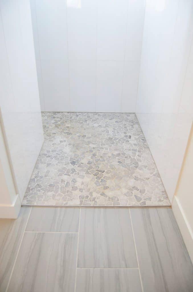pebble tile floor walk in shower white vertical tile