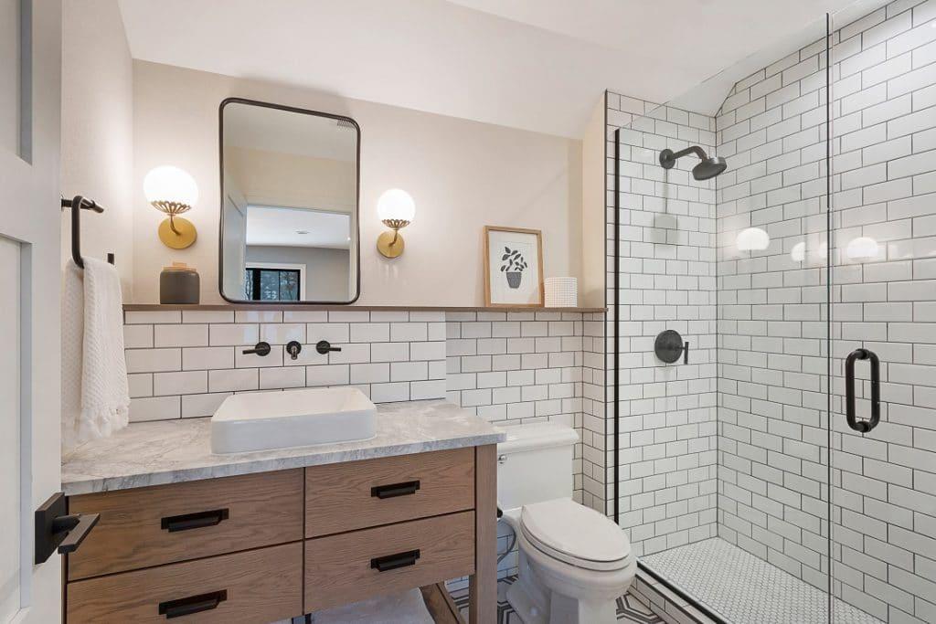 coastal farmhouse style bathroom white subway tile black grout shower wainscoting