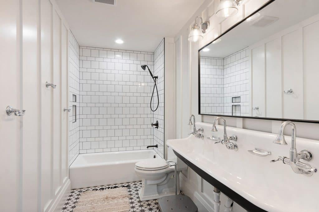 coastal farmhouse bathroom two white tile shower black gout painted tile floor