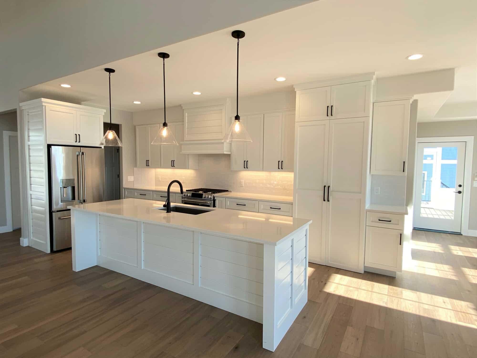 white kitchen hardwood floor white tile backsplash